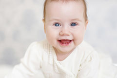 Portrait of a crawling baby on the bed in her room Stock Image