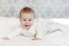 Portrait of a crawling baby on the bed in her room Royalty Free Stock Photography