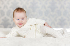 Portrait of a crawling baby on the bed in her room Stock Photography