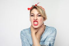 Portrait of crazy angry young woman in casual blue denim shirt with makeup and red headband standing, choke sheself and clenching. Teeth, hand on neck. indoor stock photos