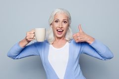 Portrait of crazy coffee lover. Joyful happy excited grandmother stock photo