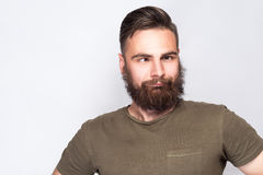 Portrait of crazy cross eyed bearded man with dark green t shirt against light gray background. Royalty Free Stock Photo