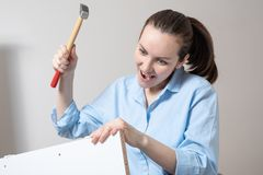 Portrait of crazy funny woman with hammer collects furniture.  royalty free stock photos