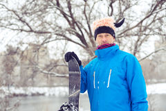 Portrait of crazy man in a funny hat with snowboard. Standing in the city park and preparing to ride. Toned image Royalty Free Stock Photography