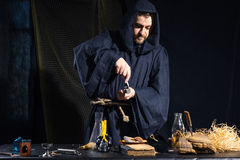 Portrait of a crazy medieval scientist working in his laboratory. Stock Images