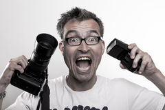 Portrait of a crazy photographer. Photographer in white T-Shirt holds a camera and a strobe in his hands while laughing and smiling Stock Image