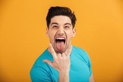 Portrait of a crazy young man in t-shirt. Showing horns up gesture isolated over yellow background Royalty Free Stock Image