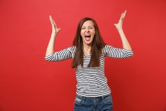 Portrait of crazy young woman in casual striped clothes screaming, rising and spreading hands isolated on bright red. Wall background. People sincere emotions royalty free stock photo