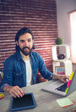 Portrait of creative businessman using graphic tablet and laptop Royalty Free Stock Photo
