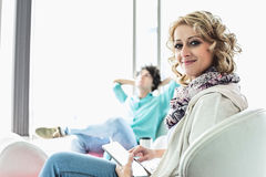 Portrait of creative businesswoman holding digital tablet at lobby with colleague relaxing in background Stock Photos