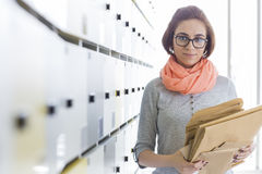 Portrait of creative businesswoman holding envelopes in locker room at office Stock Photo