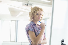 Portrait of creative businesswoman standing in front of presentation board in office Royalty Free Stock Photos