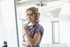 Portrait of creative businesswoman standing in front of presentation board in office Stock Photography