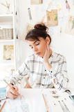 Portrait of a creative fashion designer woman working at workshop. Portrait of a young creative fashion designer woman working at workshop royalty free stock image
