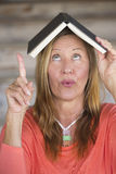 Portrait creative woman with book on head Stock Image