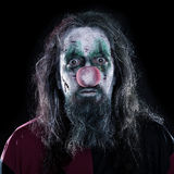 Portrait of a creepy clown in front of black background, concept Stock Photos