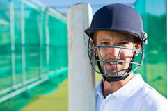 Portrait of cricket player with bat wearing helmet. Portrait of confident cricket player wearing helmet holding bat at pitch royalty free stock photos