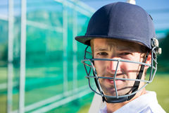 Portrait of cricket player wearing helmet. Standing at pitch stock photography