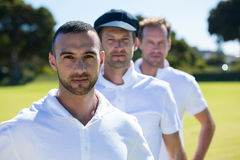 Portrait of cricket players standing at grassy field. On sunny day royalty free stock photos