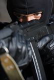 Portrait of criminal with a gun. Closeup photo of armed man in black mask Stock Photos