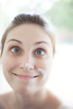 Portrait of Cross Eyed Woman with Paint on Her Fac. High key portrait of young woman decorating her home making funny face Royalty Free Stock Photos