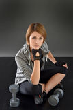 Portrait of crossfit woman sitting on the floor with weights Stock Photography