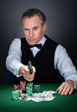 Portrait of a croupier aiming with a gun Royalty Free Stock Photography