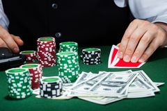 Portrait of a croupier looking at playing cards Stock Photo