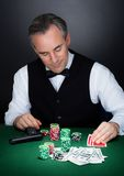 Portrait of a croupier looking at playing cards Royalty Free Stock Photos