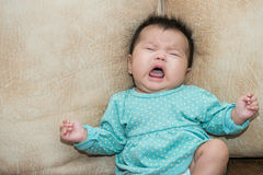 Portrait of a crying baby girl on a leather backgr Royalty Free Stock Photo