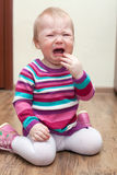 Portrait of crying baby girl on living room at home Royalty Free Stock Image