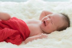 crying baby girl lying in bed stock image