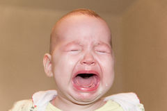 Portrait of a crying baby. Tears on the face Royalty Free Stock Images