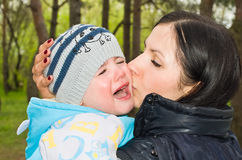 Portrait of a crying child. In mother's arms Stock Photo