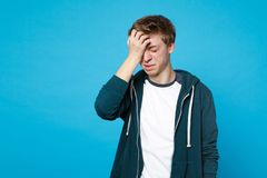 Portrait of crying displeased young man in casual clothes keeping eyes closed putting hand on head isolated on blue royalty free stock images