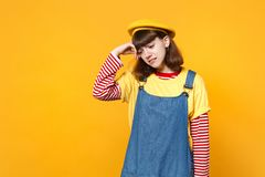Portrait of crying dissatisfied upset girl teenager in french beret, denim sundress putting hand to head isolated on stock photos