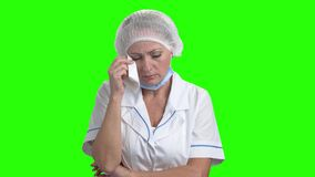 Portrait of crying doctor on green screen. Unhappy doctor woman is crying and wiping tears on chroma key background stock video footage