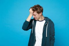 Portrait of crying frustrated young man in casual clothes with lowered head, putting hand on head isolated on blue stock photo