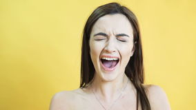Portrait of the crying girl on yellow background in 4K stock video footage