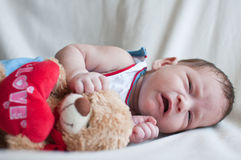 Portrait of crying Little baby with toy bear Stock Photos