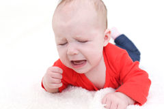 Portrait of crying 3 months baby girl in red bodysuit Stock Photos