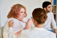Obese Young Woman Crying in Support Group Session. Portrait of  crying obese  women talking to psychiatrist during group therapy session, providing counseling Stock Images
