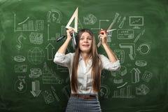 Portrait cultivé de jeune femme d'affaires dans l'effort tenant des fournitures de bureau au-dessus de sa tête Image libre de droits