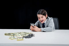 Portrait of cunning boy playing businessman and using smartphone. On black Stock Images