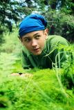 Portrait of a cunning leprechaun. Teenage boy with protruding ears, who lying on a green meadow Royalty Free Stock Photo