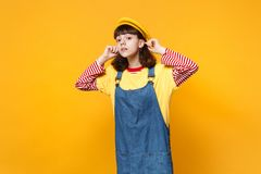 Portrait of curious girl teenager in french beret, denim sundress looking attentively far away distance isolated on stock image