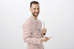 Portrait of curious handsome european gay in striped pullover, taking off glasses and waiting for boyfriend call in. Wireless earphones, holding smartphone and Stock Images