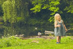 Curious little girl walking at pond in summer. Portrait of curious little Caucasian girl wearing blue dress walking at pond in summer Royalty Free Stock Images