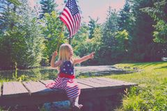 Curious girl with usa flag sitting on wooden bridge. Portrait of curious of little Caucasian girl wearing dress with stars and stripes sitting on wooden bridge Stock Image