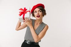 Portrait of a curious woman wearing red beret. Holding present box isolated over white background Royalty Free Stock Image